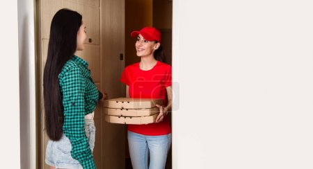 Photo pour Courier-fille souriante jeune habits rouges livré trois boîtes de pizza au client dans son appartement ou maison. - image libre de droit