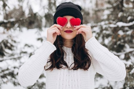 Girl holding hearts in winter nature