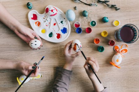 hands painting eggs