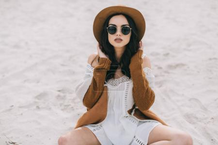 model in hat and dress on beach