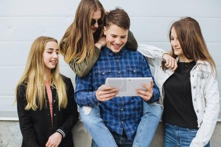 Foto de Vacaciones de verano y concepto de adolescentes - grupo de jóvenes sonrientes colgando hacia fuera, con tableta digital - Imagen libre de derechos