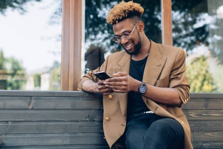 Man in a jacket with phone in city