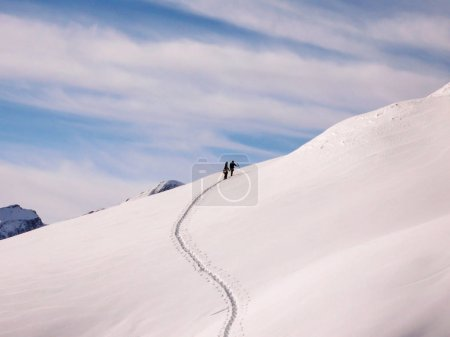 two backcountry skiers on a ski tour ascending a fresh powder snow slope in the Swiss Alps