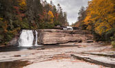 beautiful and secluded river and waterfall landscape surrounding by colorful fall foliage and forest