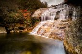 beautiful waterfall and swimming hole surrounded by colorful forest and fall foliage in late autumn
