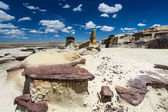 dry rock desert landscape with many hoodoos under a blue sky with white clouds