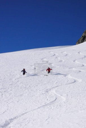 male and female backcountry skiers draw first tracks in the fresh powder snow in the Alps