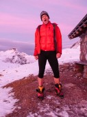 male mountain climber in red and black yawns early in the morning as the sun comes up in a pink and red sky outside of a stone mountain hut in the Alps