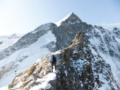 mountain guide heads towards the summit of a high alpine peak as he climbs an exposed rocky ridge