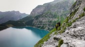 group of three men mountain climbers traverse an exposed rock ledge high above a beautiful turquoise mountain lake