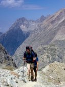 male athletic hiker on his way to a high alpine base camp for mountain climbing walks along a dusty hiking trail in the Barre des Ecrins National Park in the French Alps carrying a large backpack