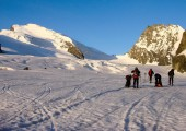 many backcountry skiers get ready to climb a high alpine peak in the Alps near Zermatt just after sunrise