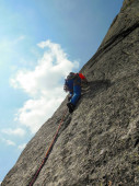 rock climber dressed in bright colors on a steep granite climbing route in the Alps