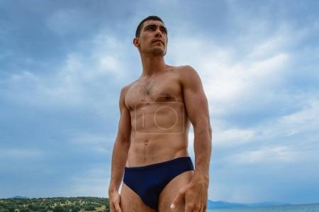 Muscular man standing on the beach in a swimming t...