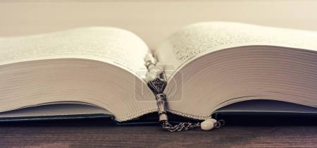 Photo for Cropped banner image of the book of the Koran with white prayer beads. shallow depth of field, DOF, toned. - Royalty Free Image