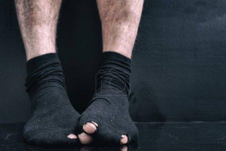 Image sous le film, les jambes dans des chaussettes trous noirs. le concept de pauvreté, de faillite, de pauvreté, de dette