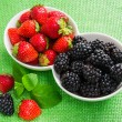 Strawberries and blackberries in a white ceramic c...