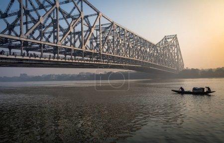 Photo pour Le pont Howrah est un pont cantilever avec une travée suspendue au-dessus de la rivière HooApproximativement au Bengale occidental, en Inde. Construit pendant le Raj britannique, il est considéré comme l'un des ponts les plus fréquentés au monde avec plus d'un véhicule lacustre traversant le pont tous les jours . - image libre de droit
