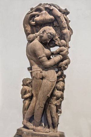 Archaeological statue of mother and child made from sandstone. Tenth century common era Khajuraho, Madhya Pradesh India.