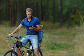 Man rides on bicycle in pine forest and looks into the phone, sport leisure.