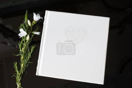 Photo pour Livre photo avec une couverture en cuir véritable. Couleur blanche avec estampage décoratif. Fond noir - image libre de droit