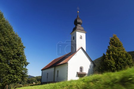 Photo for Little white  church in Slovenian countryside among lush green summer landscape and blue sky - Royalty Free Image