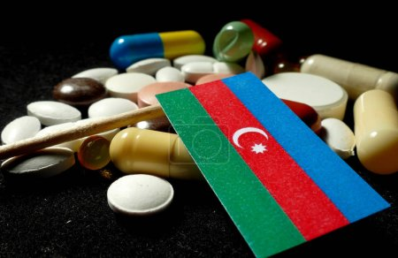 Azerbaijani flag with lot of medical pills isolated on black