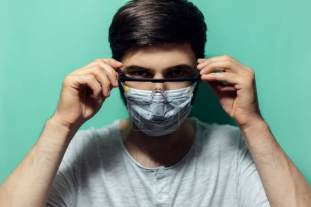 Photo for Studio portrait of young man wearing medical flu mask, puts on safety goggles against coronavirus. Isolated on background of aqua menthe color. - Royalty Free Image