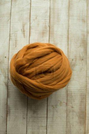 Brown merino wool ball on wooden background
