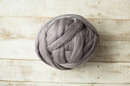 Grey merino wool ball on wooden background