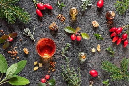 Photo pour Bouteilles d'huile essentielle avec de l'encens, de la myrrhe, de la gaulthérie, du santolina et d'autres herbes sur fond sombre - image libre de droit