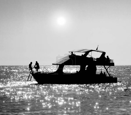 Silhouettes of people sitting on a boat.