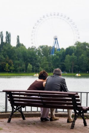 A man and a woman at an age are sitting on a park bench.
