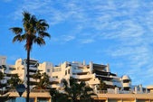 A view to a resort building at the seashore with palm trees on sunny evening, Torremolinos, Costa del Sol, Andalusia, Spain.