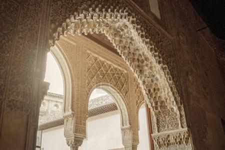 GRANADA, SPAIN - FEBRUARY 10, 2015: A close-up view to calligraphy decorated details of an archway at palace of Alhambra, Granada, Andalusia, Spain.