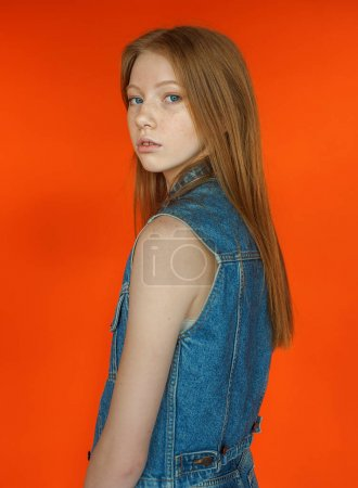 Studio portrait of teenage caucasian girl in Spring jeans outfit