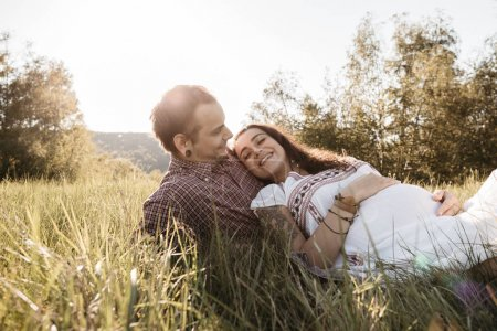 Happy pregnant couple resting on lawn enjoying themselves