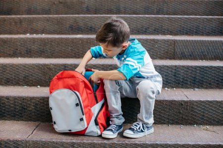 Young schoolboy checking the content of his new school bag