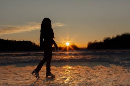 A silhouette of a woman with ice skates at sunset