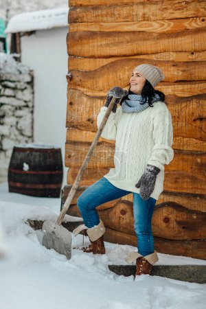 woman with snow shovel cleaning snow