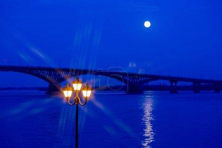 Luminoso farol en primer plano. Al fondo el puente sobre el río. Tarde o paseo nocturno en la ciudad de Saratov, Rusia. El río Volga. La luna llena