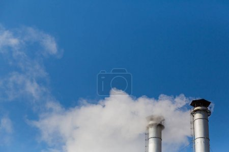 The smoke from the chimneys of a heating plant in the background of blue sky.