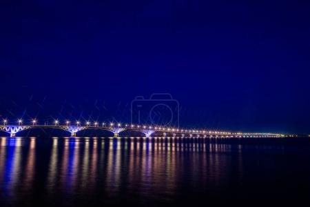 Photo pour Pont routier sur le fleuve Volga entre les villes de Saratov et Engels, en Russie. Soir de paysage ni la nuit. Lumières de la rue dorées. Le reflet dans l'eau. - image libre de droit