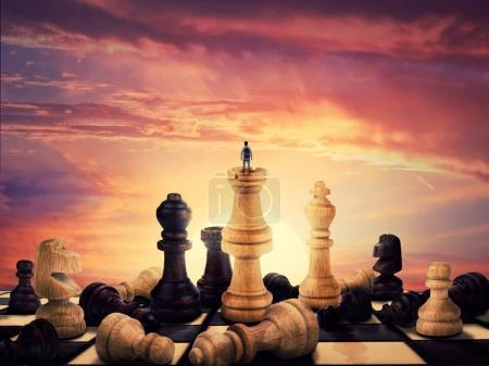 Photo for Successful boy standing on a chess piece meeting the sunrise on the horizon. Gigant chess figures scattered on the vintage chessboard. Symbol of business aspirations, freedom and leadership concept. - Royalty Free Image