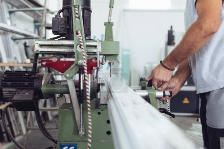 Manual worker doing job on machine for cutting