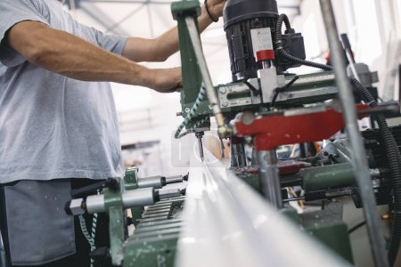 Photo for Manual worker doing his job on big machine for profile cutting. Manufacturing jobs. Selective focus. Factory for aluminum and PVC windows and doors production - Royalty Free Image