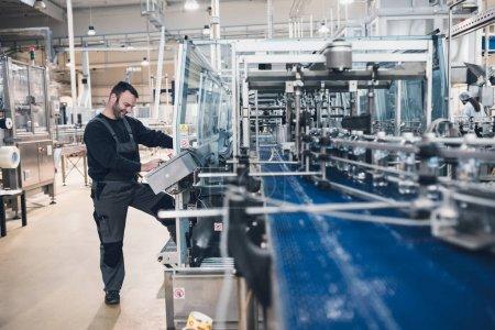 Photo pour Heureux travailleur souriant faisant son travail sur Robotic ligne d'usine pour le traitement et le contrôle de la qualité de l'eau de source pure embouteillée dans des conteneurs. Faible luminosité et faible bruit visible - image libre de droit