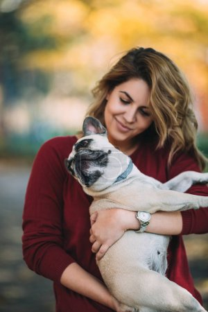People and dogs outdoors. Beautiful and happy woman enjoying in autumn park walking with her adorable English bulldog