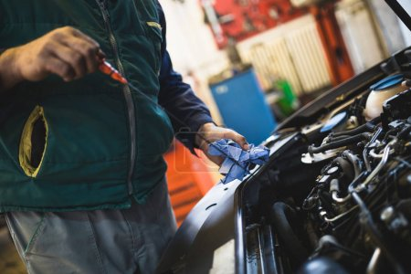 Car service mechanic working on automobile engine repair