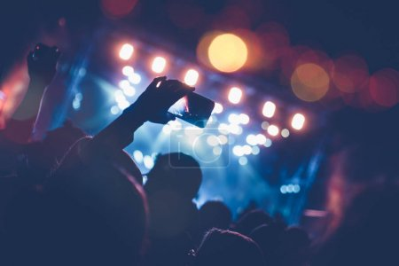 Silhouettes of festival concert crowd in front of bright stage lights. Unrecognizable people and colorful effects